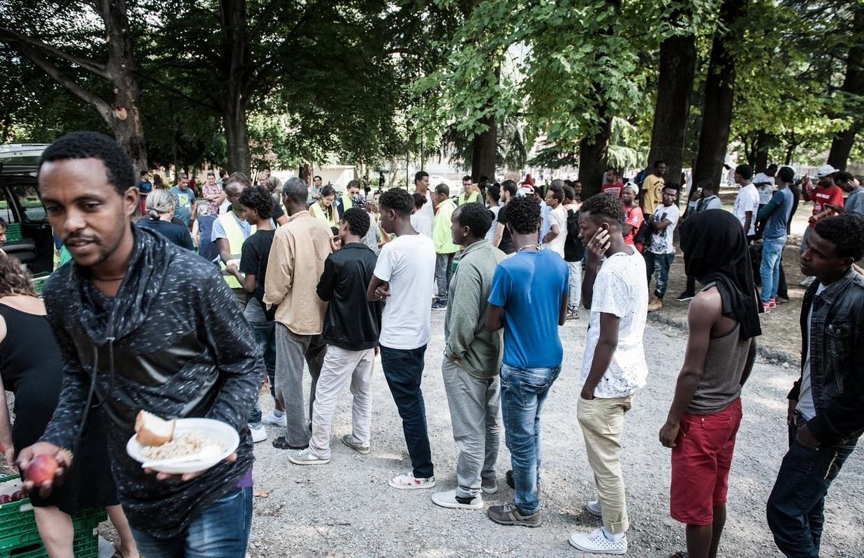 O fotojornalista italiano Mattia Vacca em Como no verão de 2016 e mostra um grupo de migrantes em um parque fora da estação ferroviária. Centenas ficaram presas na fronteira entre a Itália e a Suíça, depois que a Suíça fechou suas fronteiras para os migrantes que tentavam chegar ao norte da Europa.
